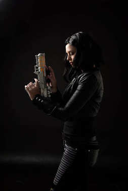 portrait of black haired girl wearing leather clothes, moody lighting on black background.
