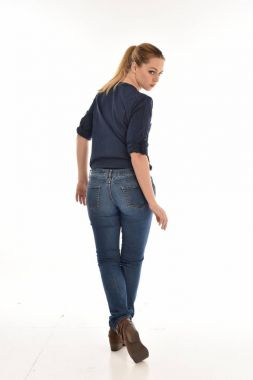 full length portrait of blonde girl wearing simple blue shirt and jeans, standing pose facing away from the camera. isolated on white background.