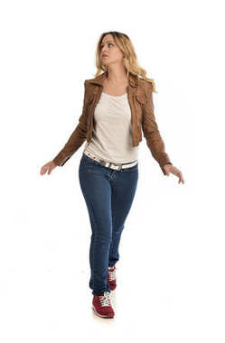 full length portrait of blonde girl wearing brown jacket and jeans. standing pose on white background.