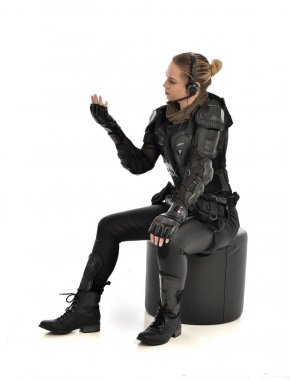 full length portrait of female wearing black  tactical armour, crouching pose, isolated on white studio background.