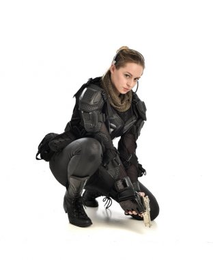 full length portrait of female wearing black  tactical armour, crouching pose and holding a weapon, isolated on white studio background.