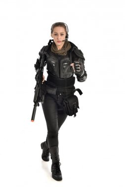 full length portrait of female  soldier wearing black  tactical armour, holding a rifle gun, isolated on white studio background.