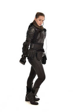 full length portrait of female  soldier wearing black  tactical armour, standing in profile, isolated on white studio background.