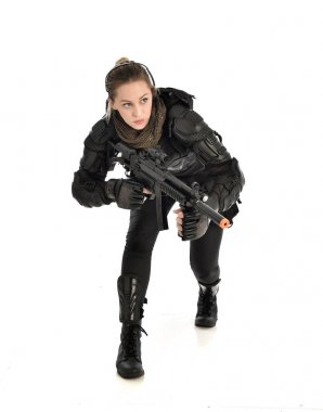 full length portrait of female  soldier wearing black  tactical armour, seated pose holding a gun, isolated on white studio background.