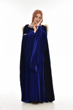 full length portrait of woman with long hair, wearing a blue velvet medieval gown and fur cloak. standing pose, isolated on white background.