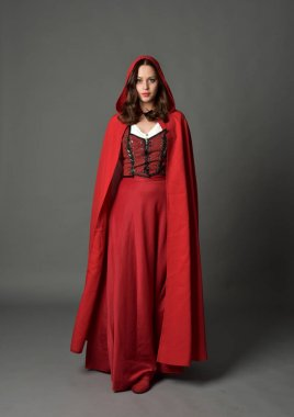 full length portrait of brunette lady wearing red fantasy costume with cloak, standing pose on grey studio background.