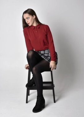 full length portrait of a pretty brunette girl wearing a red shirt and plaid skirt with leggings and boots. Sitting on a chair against a  studio background.