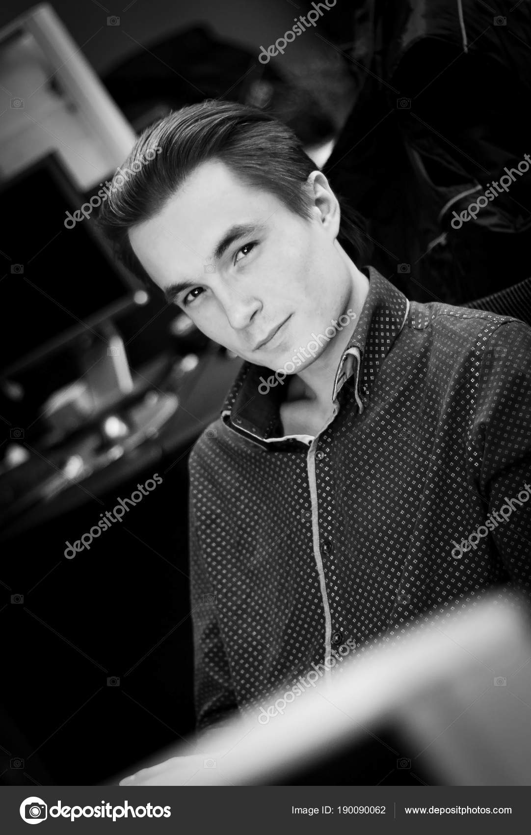 Portrait of a young cute guy in a shirt in an office setting black and white image