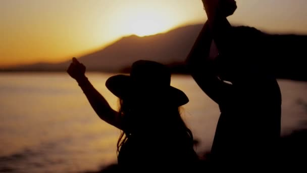 Happy couple dancing on beach enjoying honeymoon in nature at sunset . Couple enjoying a romantic sunset evening together on the beach.Couple silhouette at the beach. Lovers enjoying honeymoon. Sunset