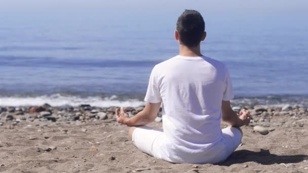junger Mann macht Meditation in Lotus-Pose am Strand, Harmonie und Kontemplation. Junge praktiziert Yoga im Seebad im Urlaub.