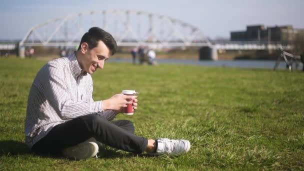 Muže, který psal masáž, venku a pití kávy. Studenti sedí na trávě chating. Pohledný podnikatel psaní masáže s papíru šálek kávy. Úsměv