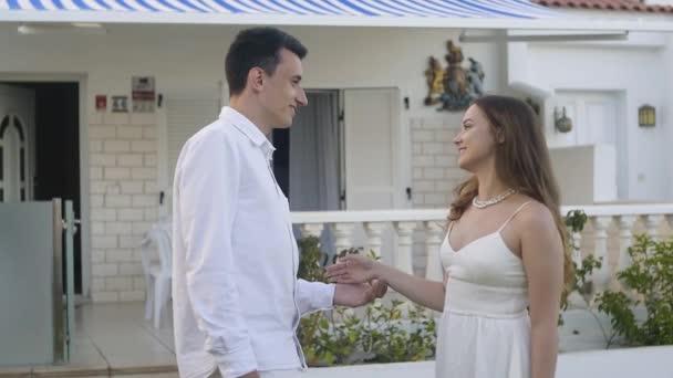 Muž s dívkou v bílých šatech na pozadí vily, doma, mluví, směje se, flirtuje. Pár na dovolené, dům k pronájmu, ideální výlet. Láska
