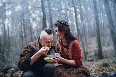 young  guy with his beloved girl eating   in the forest
