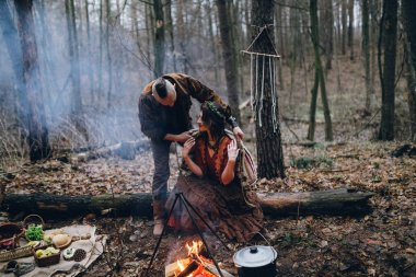 Handsome guy with his beloved girl in the forest putting coat on her shoulders