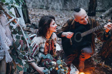 Handsome guy playing  the guitar for his beloved girl in the forest