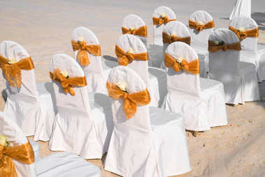 The wedding chair with spandex white cover with gold organza sash and white flowers accent, The preparation of the wedding venue on the beach at Samet island, Thailand.