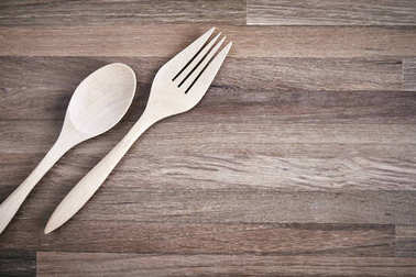 Wooden fork and spoon on the wooden floor with texture, closeup