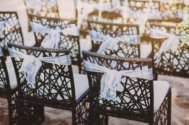 The back side of black wooden chairs with white organza sash decoration for beach wedding venue