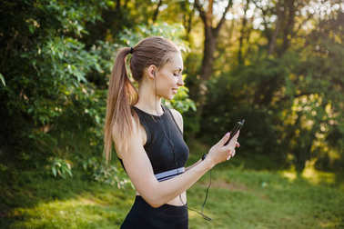 sports girl listening to music in the park