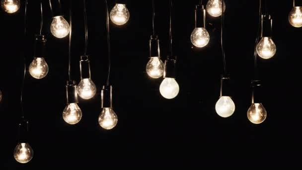 Electric bulbs are connected in a garland outside at night