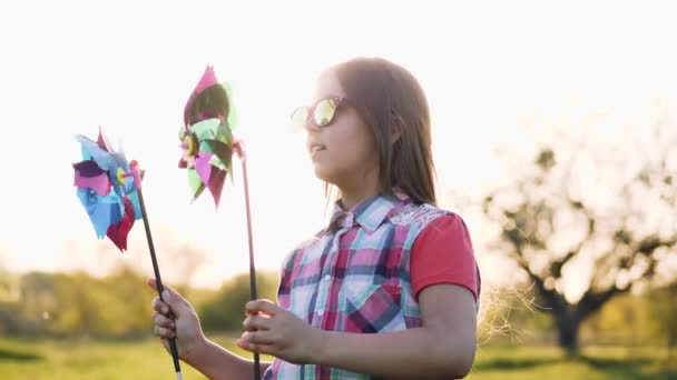 Girl funny dancing with a coloured toy windmill