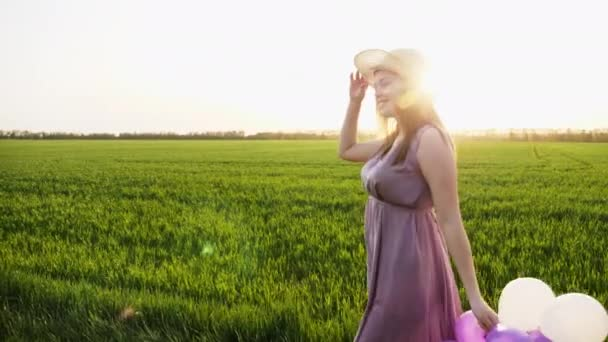 Beauty girl walking on spring field with colorful air balloons