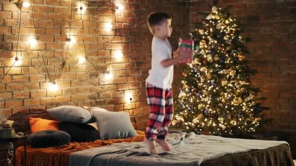 Kleiner Junge hält Geschenkbox in der Hand und springt aufs Bett