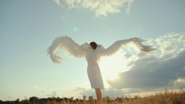 Woman in a white dress raises angel wings up
