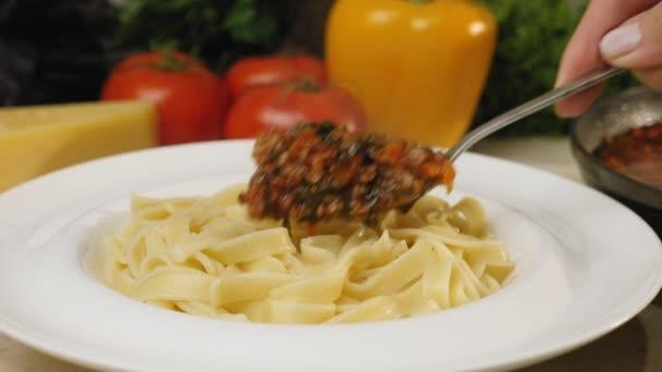 Přidání boloňské omáčky na těstoviny tagliatelle