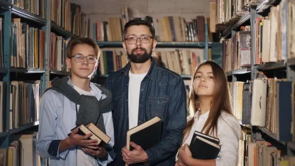 Portrét mladého knihovníka s teenagery v knihovně