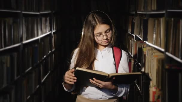 Girl with glasses reading a book in the library