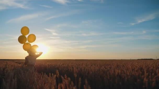 Dívka běží přes pole se žlutými balónky v ruce