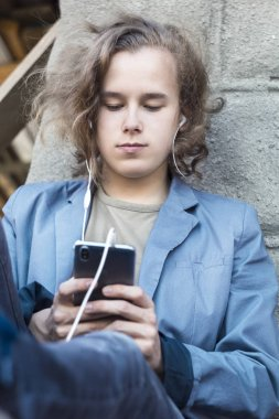 A young man holds a phone in his hand and listens to music. A boy teenager uses a gadget while sitting on the street.