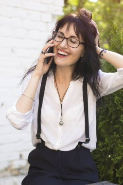 Gorgeous female is happily talking on her mobile phone. Business woman uses a smartphone outdoors.