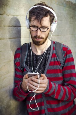 A modern young man listening to music in a smartphone against a brick wall background. Hipster uses a mobile phone, writes a message.