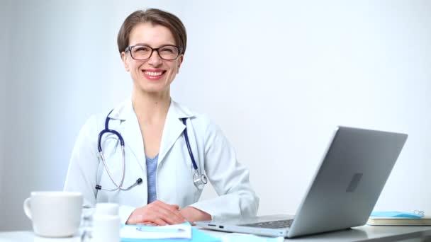 Portrét usměvavé doktorky sedící na pracovišti.