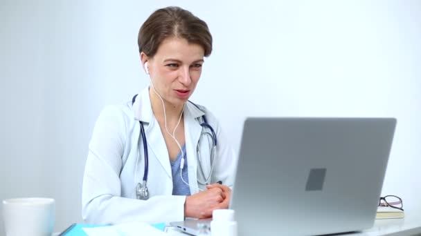Portrait of a smiling female doctor advising patient by video call in online chat on computer screen. The doctor contacts the client at the conference, talks on the laptops webcam.