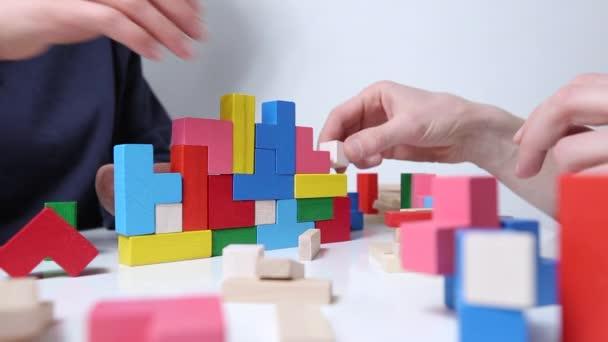Ruce muže hrajícího barevné kostky hry.