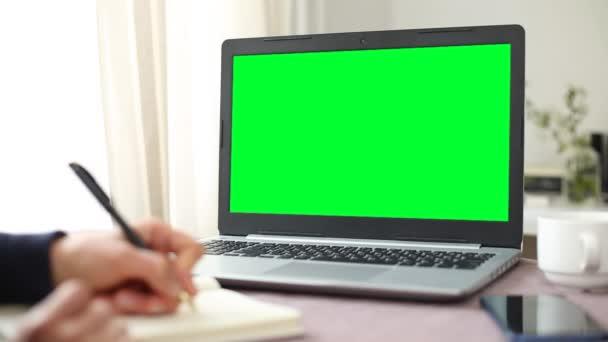 Počítačový monitor zelené obrazovky. Prázdné místo, vztyčit se. Student píše poznámky do zápisníku.