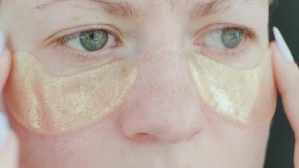 Žena vkládá náplasti pod oči osvěžující masky. Žena s kolagenovými polštářky pod očima. Kosmetické procedury. Doma. Detailní záběr