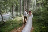 Fotografie back view of beautiful young wedding couple walking on mountain path in Alps