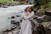 krásný šťastný svatební pár objímat a líbat horské řeky v Alpách