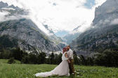 Fotografie happy bride in wedding dress and groom on green mountain meadow with clouds in Alps