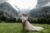 Fotografie happy bride and groom hugging on green mountain meadow with clouds in Alps