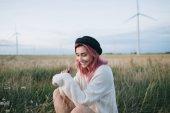 hezká dívka s růžovými vlasy v bílý svetr a čepice sedí v poli s větrnými mlýny