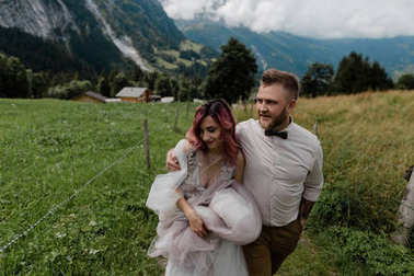 happy young wedding couple embracing and walking together in beautiful alpine valley