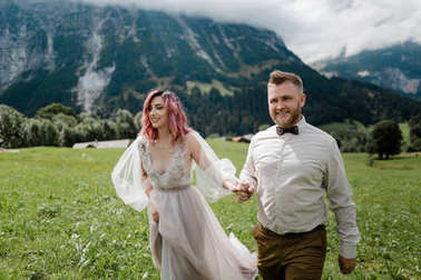 happy bride in wedding dress and groom holding hands and walking on green mountain meadow in Alps