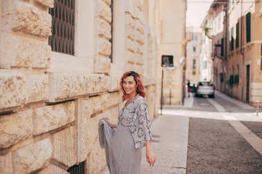 happy elegant girl in glamorous dress walking in Verona