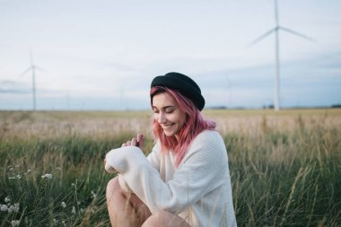pretty girl with pink hair in white sweater and hat sitting in field with windmills