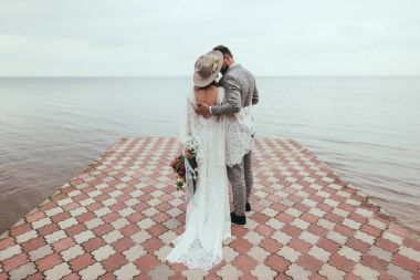 Rear view of bride and groom in boho style hugging on pier at lake stock vector